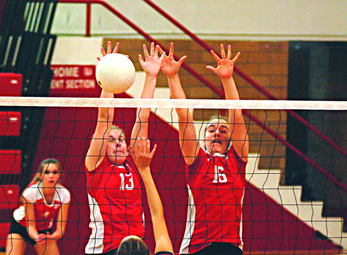 Parkersburg's Shelby Roberts (13) and Grace West (16) go up for a double block during Saturday's second annual Carl Harnish Snowball Invitational inside Memorial Fieldhouse.   Photo by  Jay W. Bennett