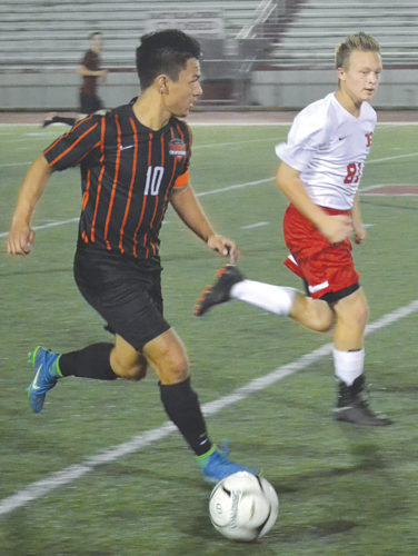 Marietta High's Austyn Chen, left, controls the ball as Parkersburg High's Caden Rogers keeps pace during a high school boys soccer match Tuesday at Stadium Field. Photo by Ron Johnston.