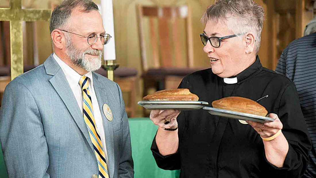 """The Rev. Janice Hill, pastor of First Christian Church in Parkersburg, presents the Rev. Jeff Allen, executive director of West Virginia Council of Churches, with two loaves of unleavened bread at the end of Tuesday's """"Compassion Calls Us"""" meeting. Hill said the loaves were a symbol of sustainable bread and will be presented at Thursday's meeting in Buckhannon. (Photo by Jeff Baughan)"""