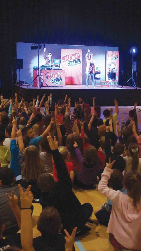 """First-graders raise their hands during Tuesday's """"Jump with Jill"""" show at West Virginia University at Parkersburg. More than 600 students from Wood and surrounding counties attended the rock and roll nutrition show. (Photo by Michael Erb)"""