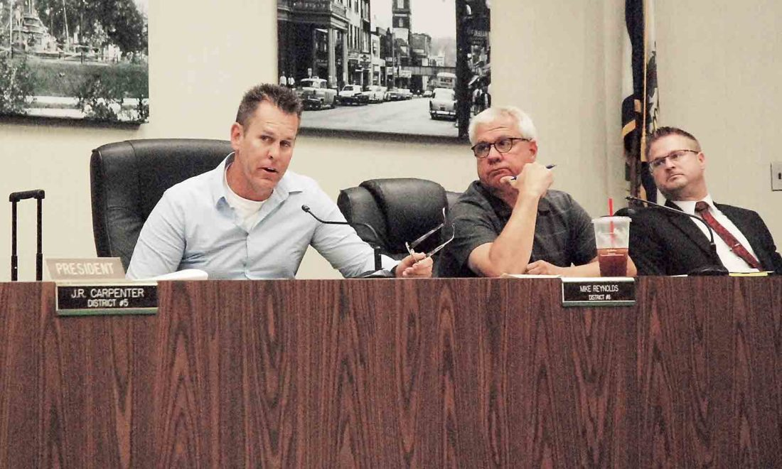 Parkersburg City Councilman Mike Reynolds, left, speaks during Tuesday's council meeting at the Municipal Building, as Councilmen John Reed and Zach Stanley listen. (Photo by Evan Bevins)
