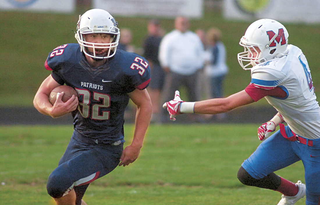 Photo by Joe Albright Parkersburg South's Tyee Gibson runs by the outstretched arm of Morgantown's Luke Milne in a Week 2 showdown between the Patriots and Mohigans.
