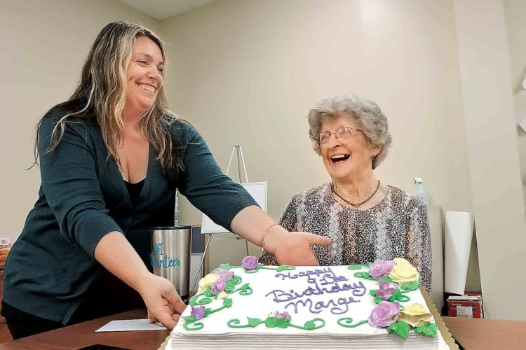 Marietta Home Health and Hospice aide Dusty DeLancey, left, helps longtime volunteer Marge Stacy show off her cake during an early birthday celebration at the hospice office Thursday. Stacy turns 91 on Tuesday. (Photo by Sam Shawver)
