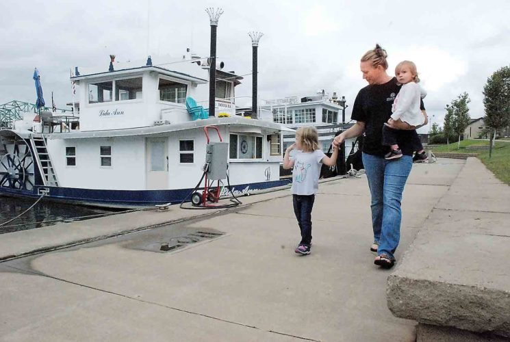Lubeck resident Terri Fleak and her daughters, Abrianna, 4, and Addy, 1, walk through Point Park Thursday, checking out the sternwheelers lined up for this weekend's Riverfest. Multiple sternwheelers are docked at the park for Riverfest, a free, family-friendly event that kicks off tonight, with opening ceremonies at 5:30 p.m. (Photo by Evan Bevins)