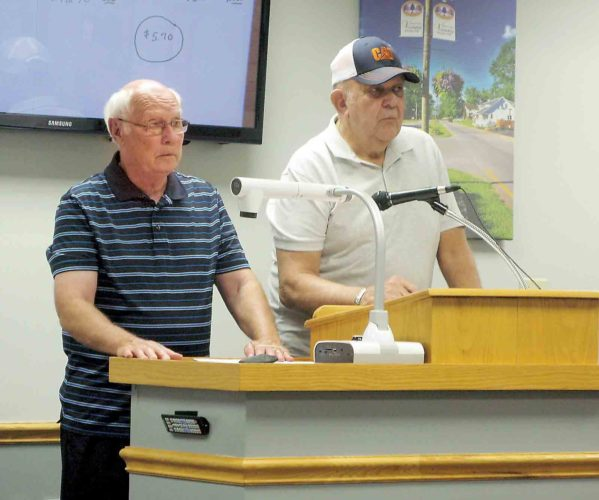 Vienna residents Joe Brookover, left, and Paul Yeater, right, presented the council with a petition they circulated in opposition to proposed rate increases for water and sewer service. (Photo by Jeffrey Saulton)