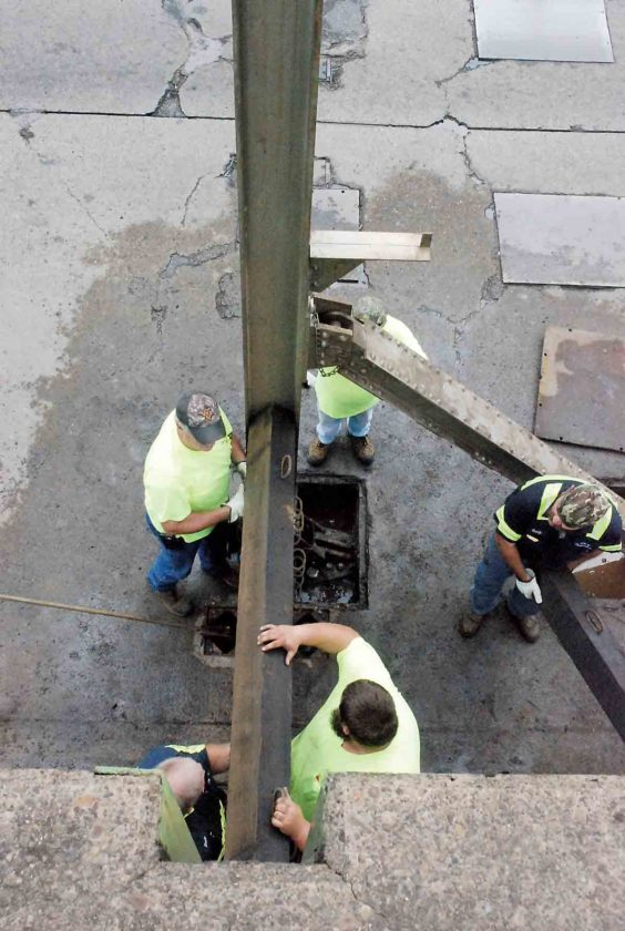 Photo by Evan Bevins City of Parkersburg employees, clockwise from bottom left, Buck McCroskey, John Flynn, Joe Nelson, Randy Foutty and Al Duley install stop logs in a bay of the floodwall in the 3400 block of Murdoch Avenue Wednesday morning.