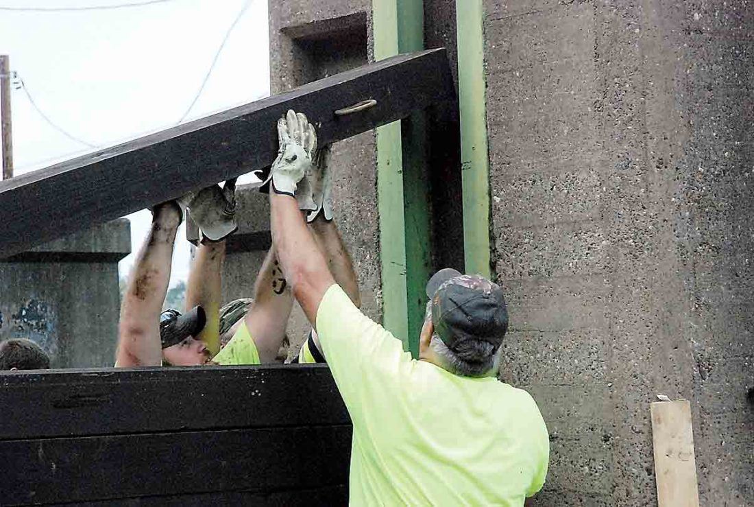 Photo by Evan Bevins City of Parkersburg employees lower a stop log into place at the Murdoch Avenue floodwall gate Wednesday.