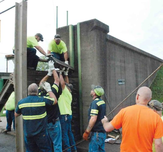 Photo by Evan Bevins City of Parkersburg employees assemble a portion of the floodwall in the 3400 block of Murdoch Avenue Wednesday morning as part of the inspection of the system by the U.S. Army Corps of Engineers.