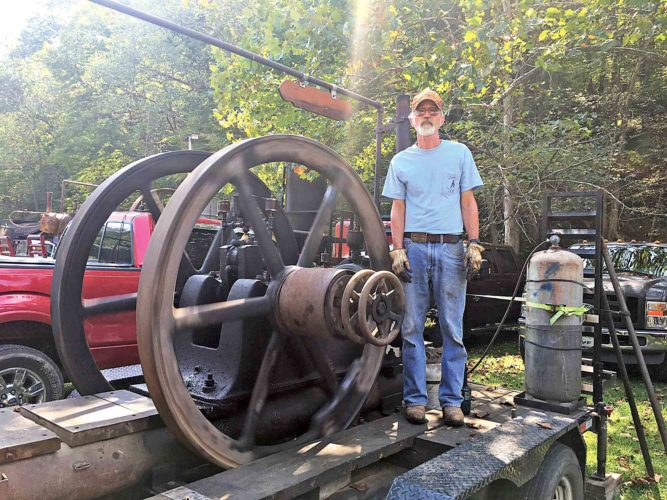 File Photo Jim Boston, of Ritchie County, stands by his 15 hp Reed motor, which is 100 years old and still running, during last year's Volcano Days Antique Engine Show and Festival at Mountwood Park.