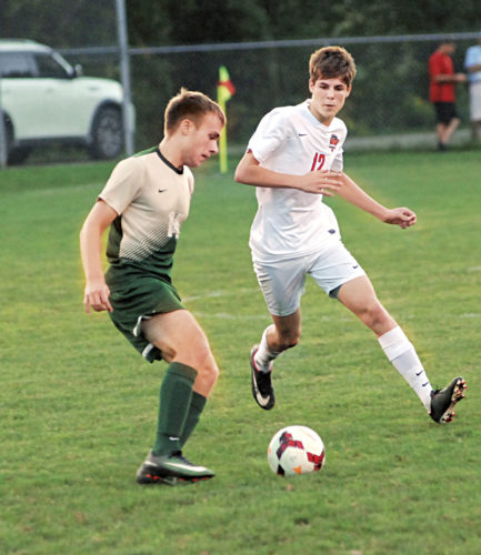 Photo by Jordan Holland Marietta High's Ryan Mannix (12) watches as Athens' Bradley Ridpath (14) makes a move with the ball during a high school boys soccer match Thursday evening at Jerry Brock Field in Devola, Ohio. Marietta won, 4-1.