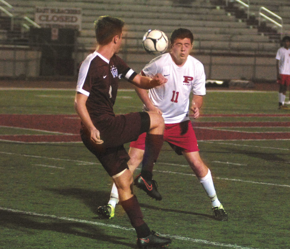 Photo by Jay W. Bennett Parkersburg's Matt Runyon narrowly escaped a ball to the head which was deflected by George Washington's Chance Anderson during Thursday night's showdown at Stadium Field. The top-ranked and Class AAA defending state champion Patriots were upended by the host and sixth-ranked Big Reds, 2-1, which snapped a 38-match unbeaten streak for GWHS.