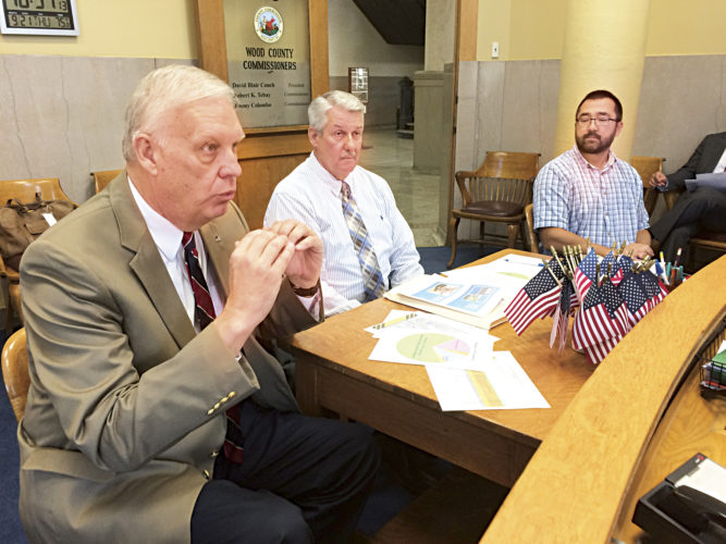 Photo by Brett Dunlap Bob Ashley, Gov. Jim Justice's legislative director; Rusty Roten, West Virginia Division of Highways District 3 engineer, and Dave Burris, maintenance engineer for DOH District 3, discussed road projects with the Wood County Commission Thursday.