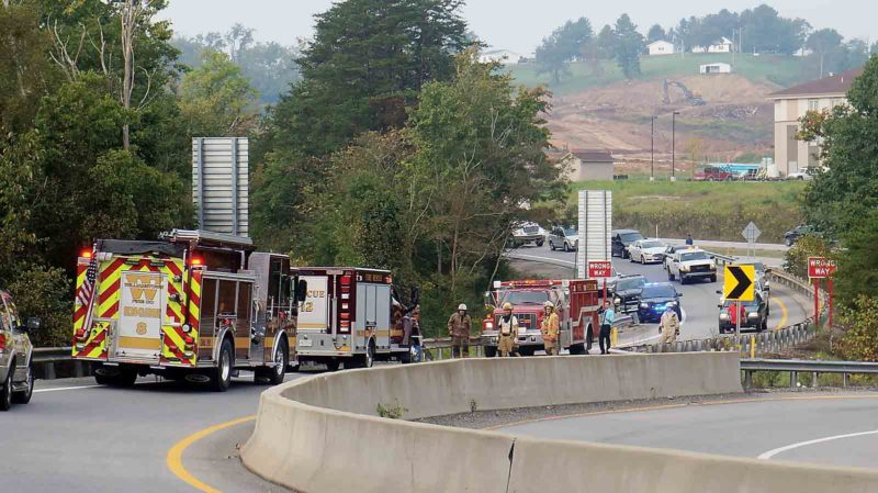Photo by Michael Erb First responders gather on Ashby Ridge Road near the Interstate 77 Emerson Avenue exit after a truck went through a fence, up a hill and struck the back side of the exit ramp's guardrail. The driver suffered only minor injuries and was not cited.