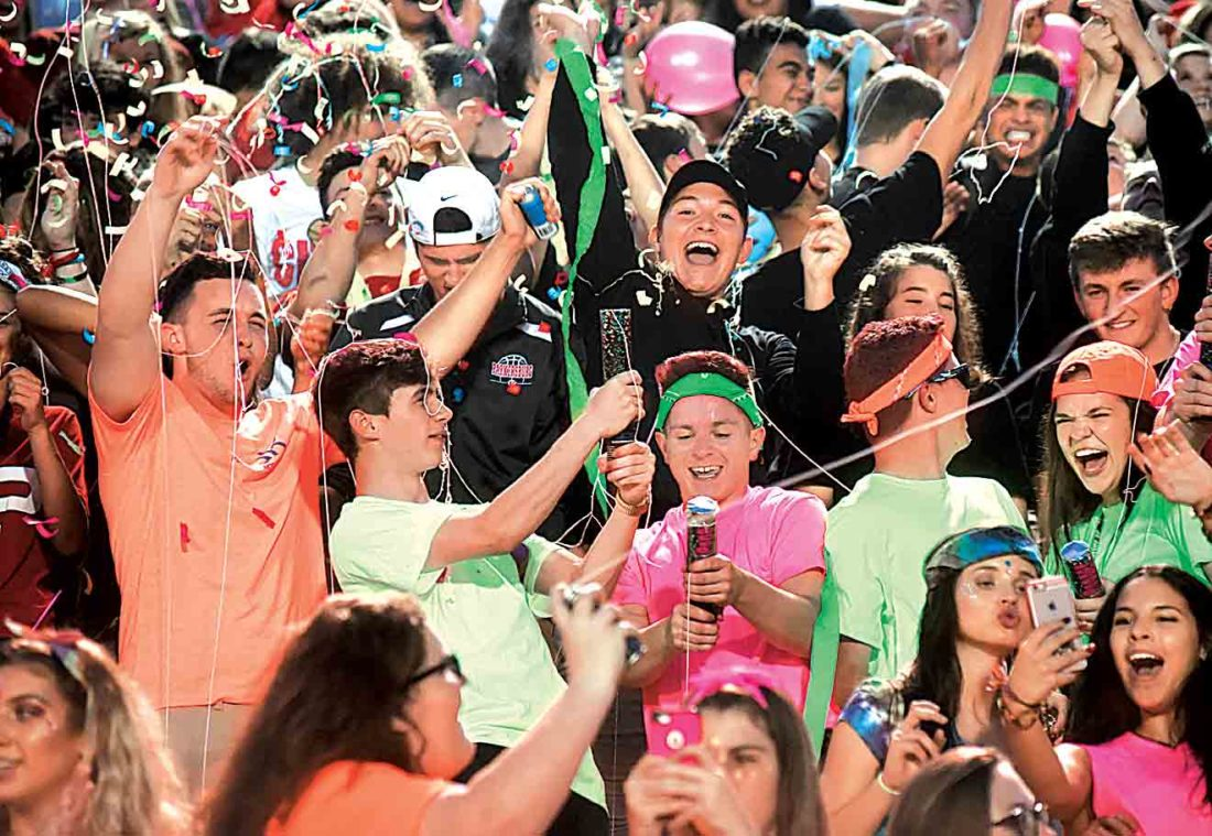 Photo by Jeff Baughan Parkersburg High School students set off noise makers and confetti poppers after the first tackle was made Friday night during the Big Reds' win over Marietta High School at Stadium Field.