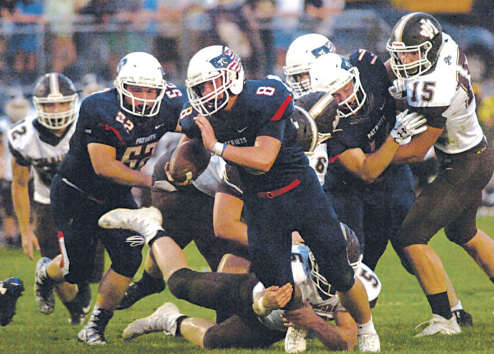 Parkersburg South's Nick Yoho tries to dance out of the attempted tackle from John Marshall's Charles McCool during the Monarchs' 40-17 win over the Patriots. Photo by Joe Albright.