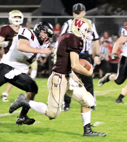 Williamstown quarterback Carter Haynes runs away from Ravenswood's Evan Dunlap (1) during the Yellowjackets' 52-14 homecoming victory versus the Red Devils on Friday night. Photo by Michael Uhl.