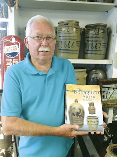 """Photo by Dreama Alderman-Suek Jim Stage, a partner in the Williamstown Antique Mall and an authority on Donaghho Pottery, poses with his book, """"The Donaghho Story."""" The book will be available around the first of October."""