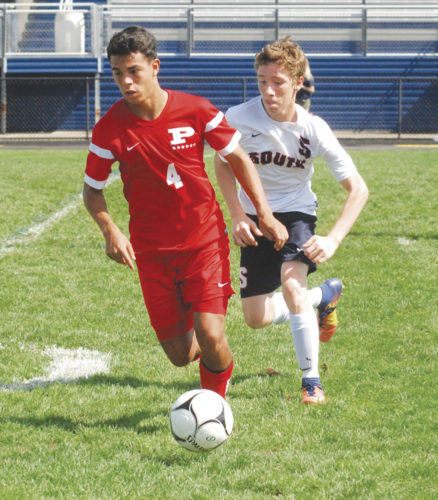 Parkersburg South's Julio Lemas (5) chases Parkersburg's Isaiah Owen (4) with the ball during a boys soccer match Saturday afternoon at the Erickson All-Sports Facility. The host Patriots scored first, but the Big Reds won, 4-1. Photo by Steve Hemmelgarn.