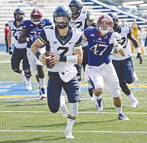 West Virginia quarterback Will Grier (7) runs for a first down during the second half of an NCAA college football game Saturday against Kansas  in Lawrence, Kan. West Virginia won 56-34 (AP Photo).