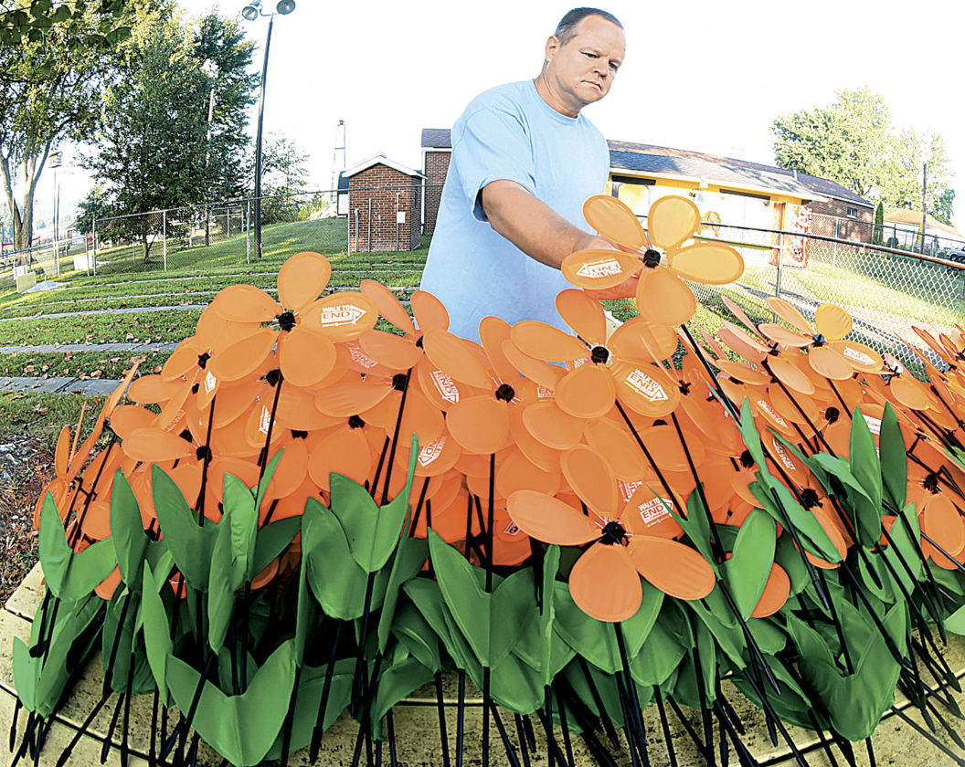 Photo by Jeff Baughan Mike Elam, administrator at Care Haven of Pleasants in Belmont, assembles flowers before the start of Saturday's Walk to End Alzheimer's at Tomlinson Park in Williamstown.