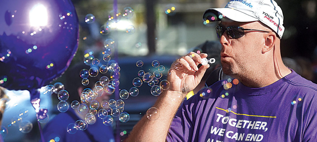 Photo by Jeff Baughan Jason Schoonmaker of Hamilton, Va., blows bubbles for his children before the start of Saturday's Walk to End Alzheimer's at Tomlinson Park in Williamstown.
