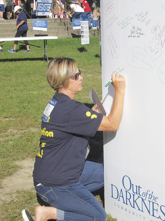 "Photo by Wayne Towner Karen Anderson,  of Vincent, signs the ""Be the Voice"" display Saturday at the 10th annual Out of the Darkness Community Walk at City Park in Parkersburg."