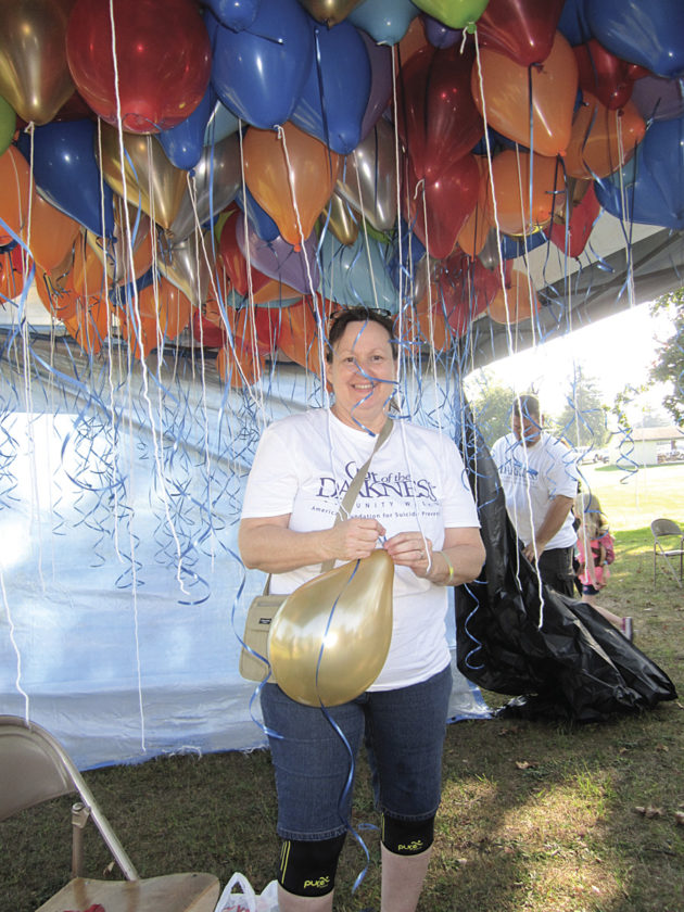 Photo by Wayne Towner Volunteer Susan Gainer, of Washington, W.Va., works to prepare balloons for the final balloon release ending Saturday's 10th annual Out of the Darkness Community Walk at City Park in Parkersburg.