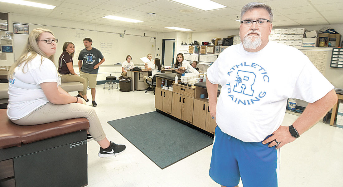 Photo by Jeff Baughan Ripley High School Athletic Director and Athletic Trainer Steve Lough MS, ATC/R, AR,  right, awaits players to come to his office/training room for pre-game taping.