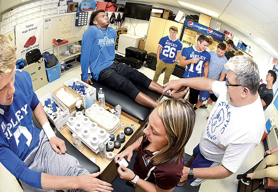 Photo by Jeff Baughan Ripley High School football player Rocky Ford, left, awaits taping of his hand to begin by Lexi Price while Ripley High School Athletic Trainer Steve Lough puts a pre-wrap spray on the ankle of Ty Eshenaur before taping it.