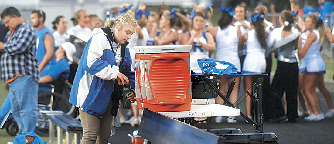 Photo by Jeff Baughan While cheerleaders and band members celebrate a first period Ripley touchdown, athletic training student assistant Anna Kimble fills water bottles for players.