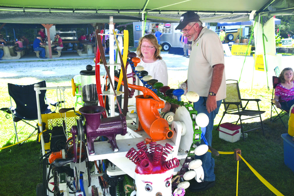 """Photo by Brett Dunlap Linnie Johnson, of Washington, W.Va., and Paul Myers, of Parkersburg, were looking at the """"Do Nothing Machine"""" during the 29th annual Volcano Days at Mountwood Park on Sunday."""