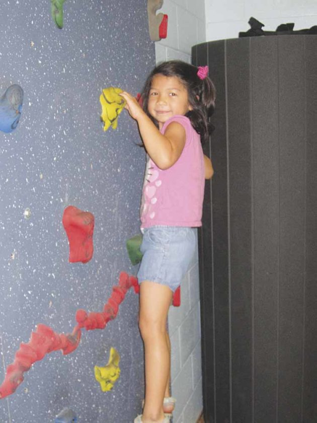 Photo by Wayne Towner Josephine Myers, 6, of Parkersburg, enjoys the climbing wall Saturday during the fourth annual  Day For Kids at the Boys and Girls  Club of Parkersburg on Saturday.