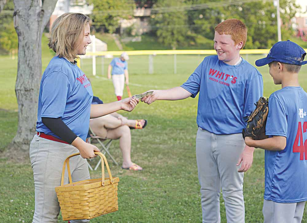 Photo by Janelle Patterson Hollis Sturgill, 12, of Warren Township, sells baked goods to brothers Ethan,11, center, and Jacob Berg, 12, right, to raise the final dollars in her $2,000 fundraising goal for the Brooks family while at her baseball game in Marietta.