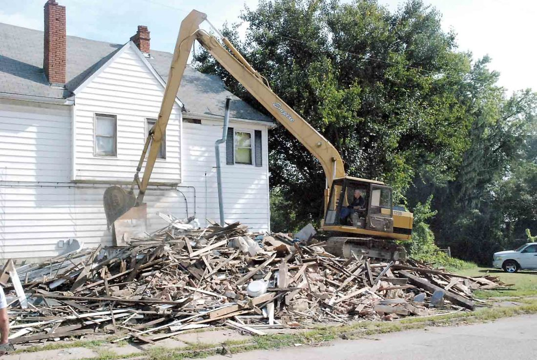 Empire Builders owner Hank Oldaker goes over the debris from a demolished house Monday at 1100 Swann St., Parkersburg. That house brings the number of dilapidated houses razed in Parkersburg in the last two years to 50. (Photo by Evan Bevins)