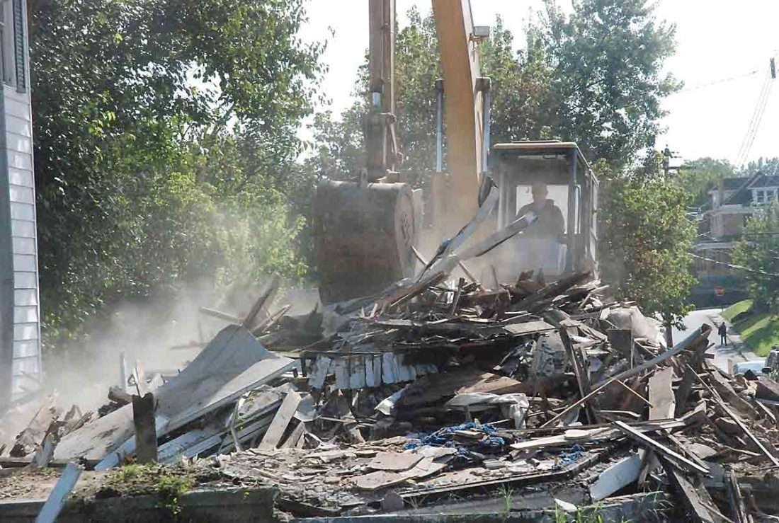 Empire Builders owner Hank Oldaker digs in the debris of a house his company demolished Monday morning at 1100 Swann St. in Parkersburg. That brings the number of dilapidated houses razed in Parkersburg in the last two years to 50. (Photo by Evan Bevins)