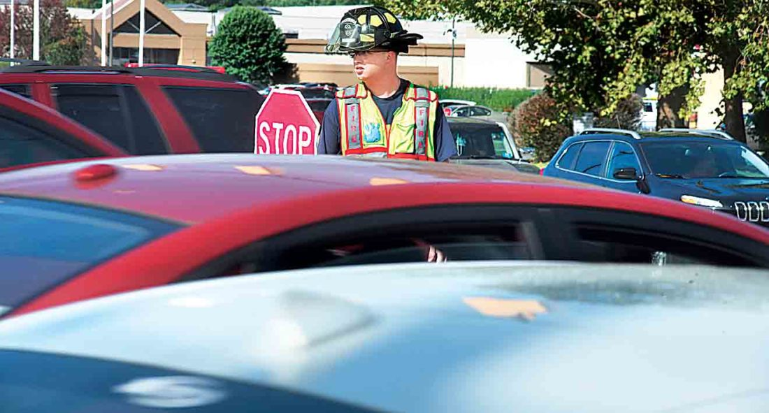 Brad Smith of the Vienna Volunteer Fire Department stands in the turn lane going into Grand Central Mall with a stop sign as firefighters became traffic directors in front of the mall Monday. (Photo by Jeff Baughan)