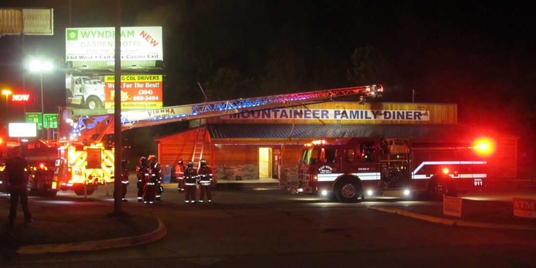 The aerial ladder from the Vienna Volunteer Fire Department hovers above the Mountaineer Family Diner where a fire occurred after 5 a.m. today.