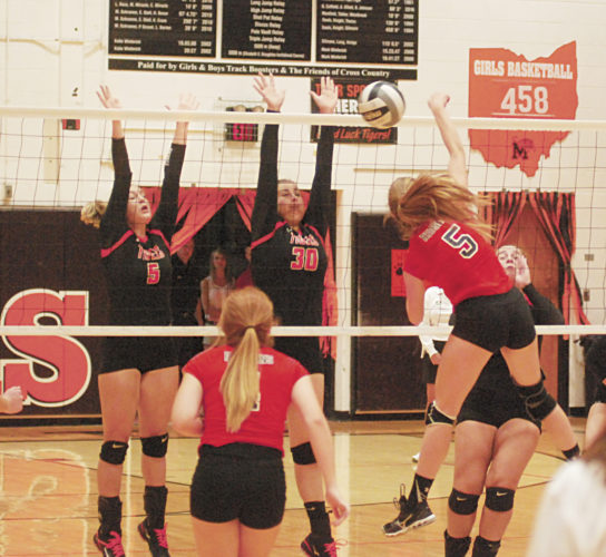 Photo by Jordan Holland Marietta's Kaitlyn McClead (5) and Jillian Middleton (30) attempt to block a spike by Coshocton's Kendall Shaw during a high school volleyball match Tuesday at Sutton Gymnasium.