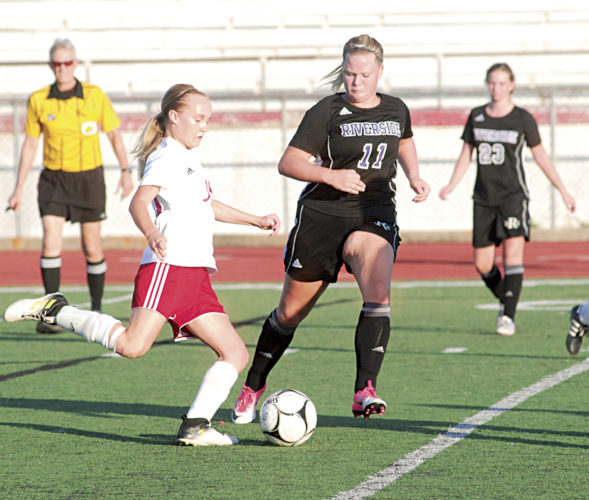 Parkersburg High's Madison Spears (left) maneuvers the soccer ball as Riverside's Kaylee Hudnall (11) closes in on her during the host Big Red girls' 5-0 win over the Warriors Tuesday evening at Stadium Field. Photo by Steve  Hemmelgarn