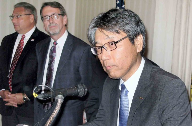 Photo by Jeffrey Saulton Takashi Ono, president of Hino Motors Manufacturing, listens during a press conference Wednesday as George Daniels, left, director of marketing and sales, and Steve Stalnaker, middle, plant manager, listen.
