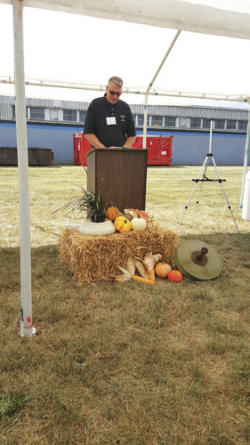 Photo provided by Mark Cenit Local pastor Chris Skeens delivers the invocation at an event Thursday marking the completion of the first phase of remediation by Applied Partners Inc. at the former Century Aluminum property near Ravenswood.