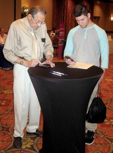 Photo by Jeffrey Saulton Monty Craig, left, and Zane Ullman, right, both of Parkersburg, talk about some of the prospects Ullman was looking at during the Parkersburg News and Sentinel Job Fair.
