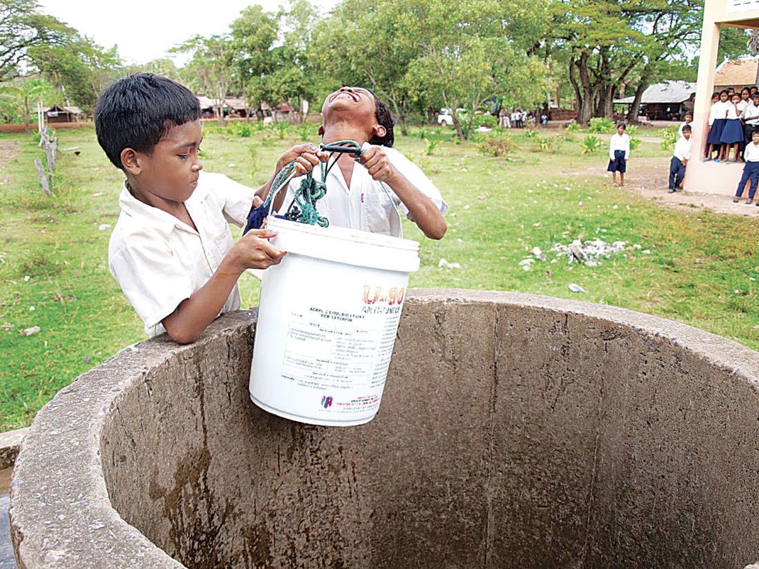Photo Provided Young Cambodian boys haul a bucket of water from a well while other school children watch.