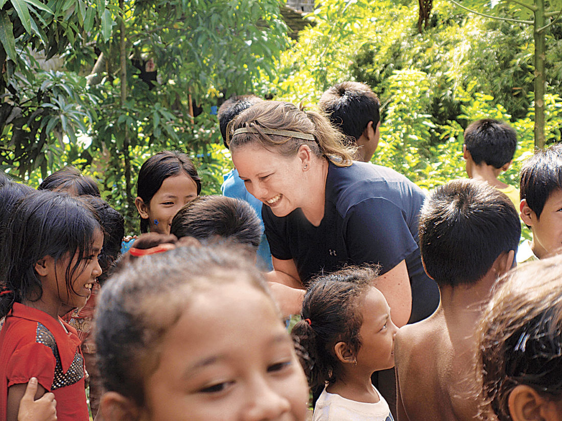 Photo Provided Lori Frees distributes items to Cambodian school children during a visit with Alongsiders International, a children's mentoring group of which Frees was a part.