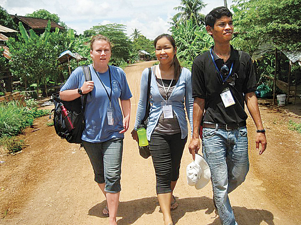 Photo Provided Lori Frees walks with friends as they make their way through a Cambodian village.