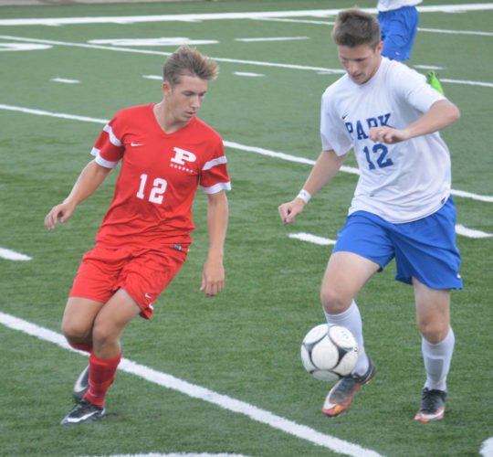 Wheeling Park's James Hofmann, right, moves with the ball as Parkersburg's Jonathan Mason closes in during Tuesday's game at Wheeling Island Stadium. The Big Reds won, 3-2.  Photo by  Josh Strope