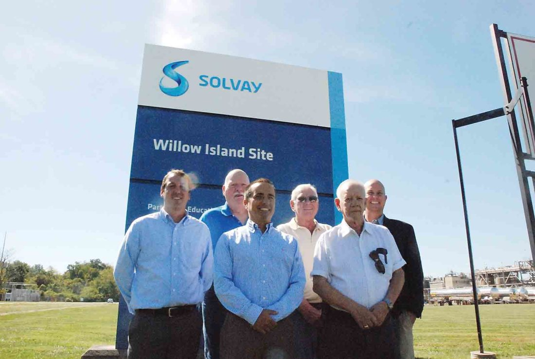From left, David Fenton, site manager at Solvay's Willow Island Site; Pleasants County Commissioner Larry Barnhart; Jeff Maley, vice president of operations for Technology Solutions of the Solvay Group; Carl Guthrie, executive director of the Pleasants County Economic Development Authority; County Commissioner Jim Cottrill; and Commissioner Jay Powell stand in front of the sign for Solvay's Willow Island Site this week before discussing the planned $70 million expansion at the facility, which is expected to create an additional 30 to 40 jobs. (Photo by Evan Bevins)