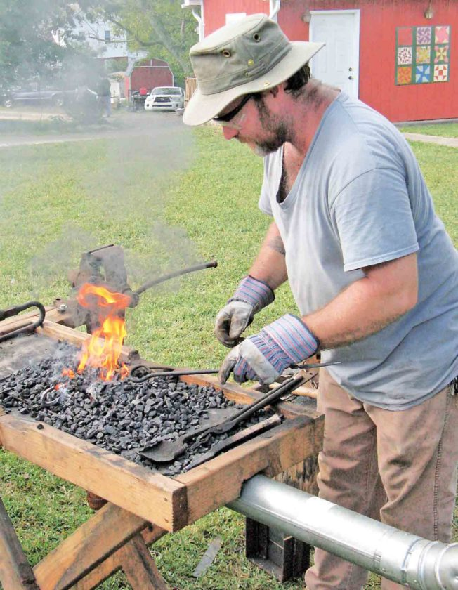 File Photo Rob Pitts, of Elizabeth, shows how blacksmiths could make a variety of things for the farm or home, such as a kettle hook for holding a pot or kettle over an open fire, at last year's Pioneer Day.