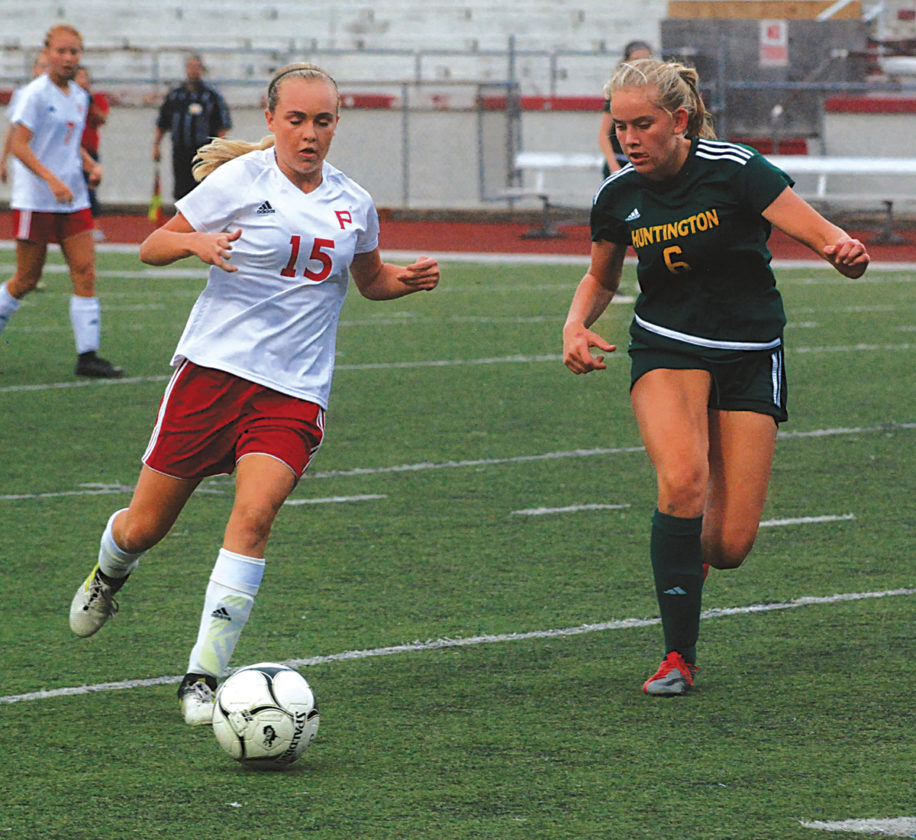 Parkersburg High's Madison Spears (15) controls the ball while being chased by Huntington's Abby Bauer (6) during a girls soccer match Thursday night at Stadium Field. Spears had a goal and an assist as the host Big Reds won 3-1 in the MSAC fifth-place playoff game. Photo by Steve Hemmelgarn.