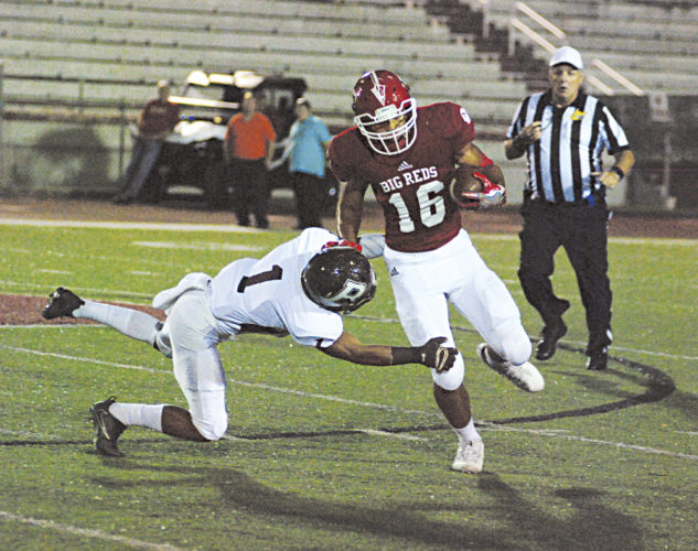 Parkersburg's Brenton Strange stiff-arms Woodrow Wilson defensive back Peyton Thomas to the Stadium Field turf during the Big Reds' 34-8 Friday night homecoming victory versus the Flying Eagles. Photo by Jay W. Bennett.